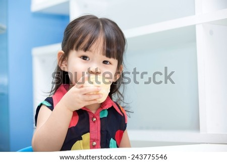 Asian cute girl eating bread  - stock photo