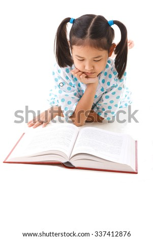 Asian cute girl reading book while lay down on floor. White background.