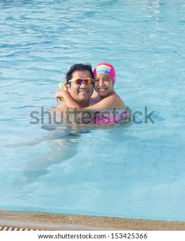 Asian dad and daughter in the swimming pool - stock photo