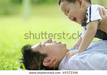 asian dad playing with son on green outdoor - stock photo
