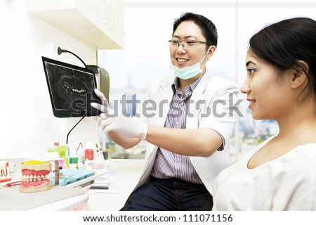Asian dentist pointing to an x-ray while explaining about the patient's teeth condition - stock photo