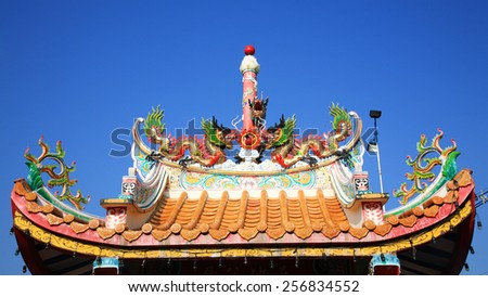Asian dragon decorated on chinese style shrine's roof against blue sky in Korat or Nakhon Ratchasime, Thailand