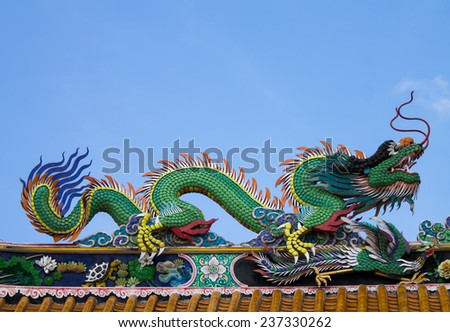 Asian dragon on top of chinese style shrine' roof, surathtani, Thailand.