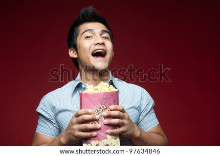 Asian eating popcorn and drinking in the movies - stock photo