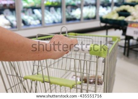 asian elderly women hand push shopping cart - stock photo