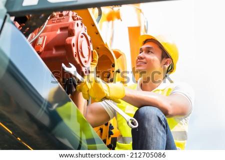 Asian engine mechanic engineer doing maintenance on machine - stock photo