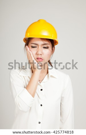 Asian Engineer girl with hard hat got toothache on gray background