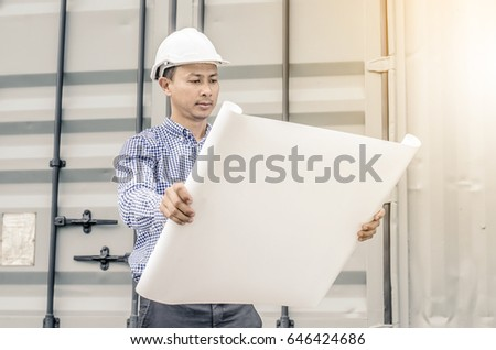 Asian Engineer man  with helmet looking paper plans at construction site.