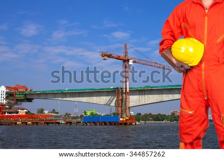 Asian engineers holding a yellow hardhat on construction site worker over the river, industrial construction concept - stock photo