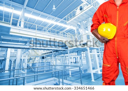 Asian engineers holding a yellow hardhat on Factory equipment inside Industrial conveyor line transporting package, industrial concept - stock photo