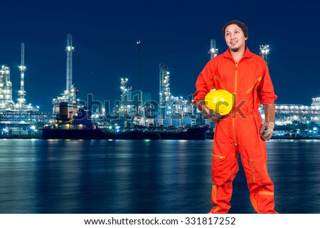 Asian engineers holding a yellow hardhat on Oil and gas refinery or Petrochemical factory at twilight time, industrial concept - stock photo