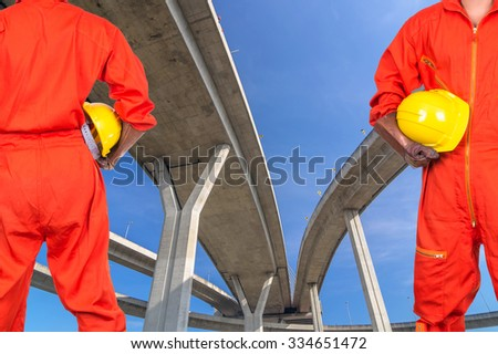 Asian engineers holding a yellow hardhat on the curve of Elevated expressway, industrial construction concept - stock photo