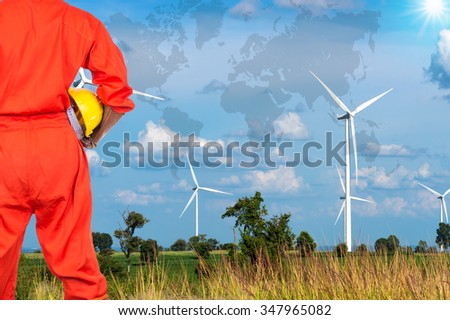 Asian engineers holding a yellow hardhat on Wind turbine power generator with world map, industrial concept, Elements of this image furnished by NASA - stock photo