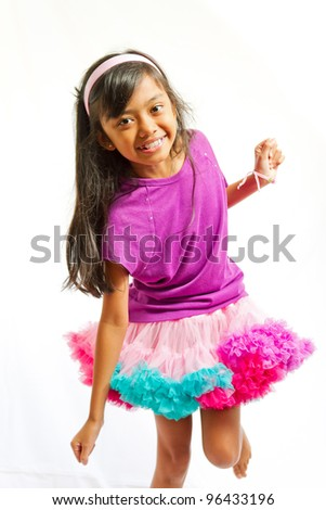 asian ethnic little girl happy dancing with tutu skirt - stock photo