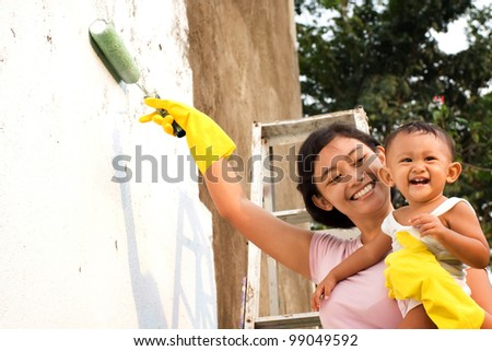 asian ethnic mother happy painting house together with child - stock photo