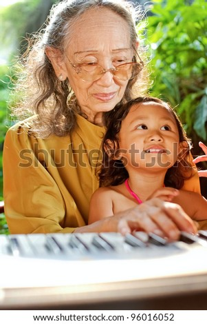 asian ethnic old woman teach child play piano - stock photo