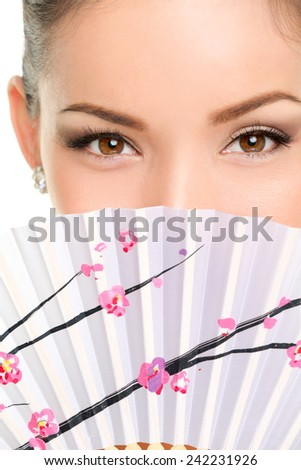 Asian eyes woman. Eye makeup asian look with paper fan. Beauty portrait of mixed race Asian / Caucasian female model on white background. Close up on eyes. - stock photo