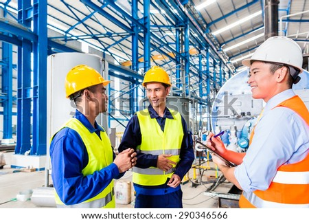 Asian factory worker and engineer as team inspecting a machine delivery - stock photo