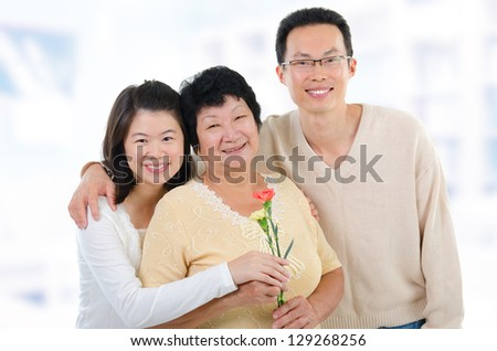 Asian family at home. Adult offspring giving carnation flowers to senior mother. - stock photo