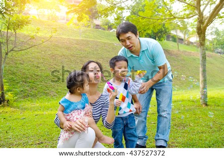 Asian family blowing bubbles outdoor - stock photo