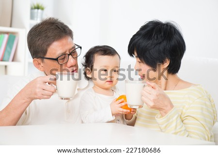 Asian family drinking milk, grandparents and grandchild indoor living lifestyle at home. - stock photo