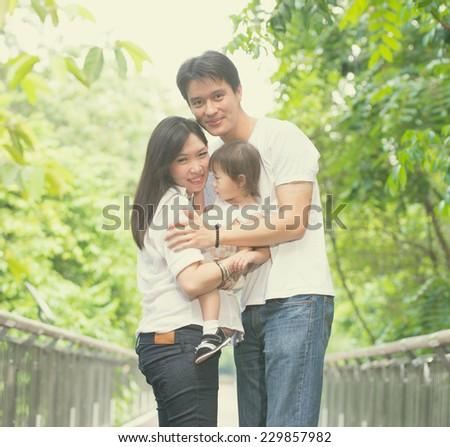 asian family enjoying outdoor park , vintage tone - stock photo