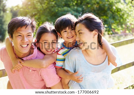 Asian Family Enjoying Walk In Summer Countryside - stock photo