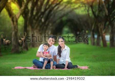 Asian family, Happy asian mother, father and daughter relax in the park - stock photo