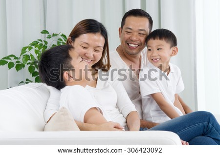 Asian family having conversation at home - stock photo