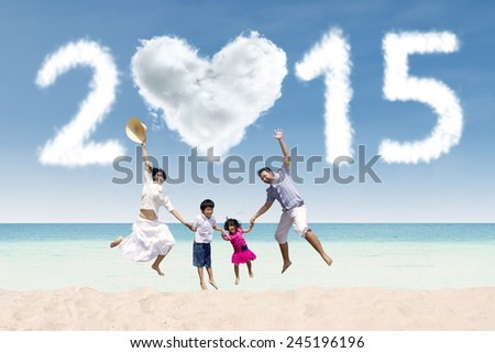 Asian family having fun at beach with cloud of 2015 - stock photo