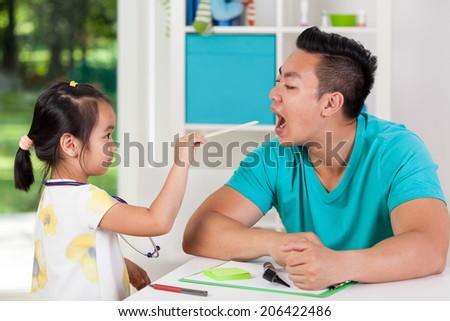 Asian family having fun at doctor's office - stock photo
