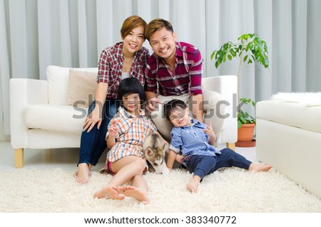 Asian family having fun time with puppy at home