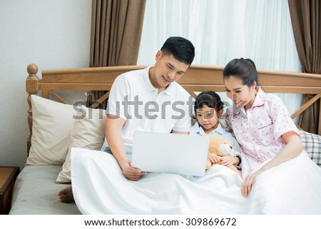 Asian family I was teaching children to use computers They lie on the bed - stock photo
