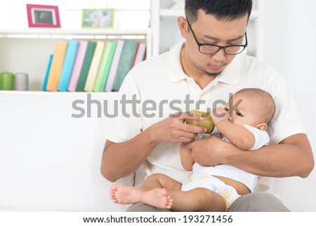 Asian family lifestyle at home. Father bottle feeding baby fruits puree. - stock photo