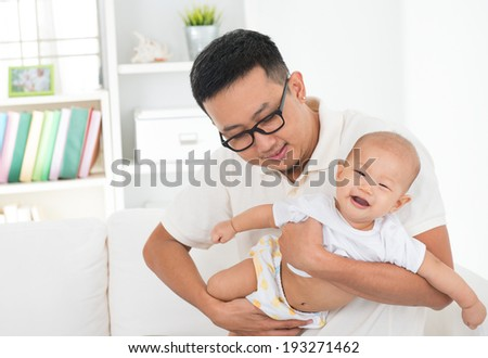 Asian family lifestyle at home. Father flying baby boy, having fun time together. - stock photo