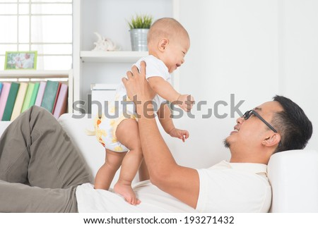 Asian family lifestyle at home. Father playing with baby boy.