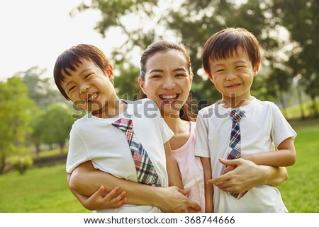 Asian family mom and two twins boys in the park in emotional parents and children relation  - stock photo