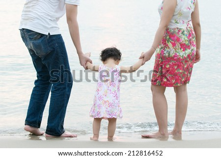 Asian family outdoor on sand beach, vacation during summer, natural sunset sunlight. - stock photo
