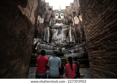 Asian family pay respect to the big buddha at srichum temple, Sukhothai thailand - stock photo