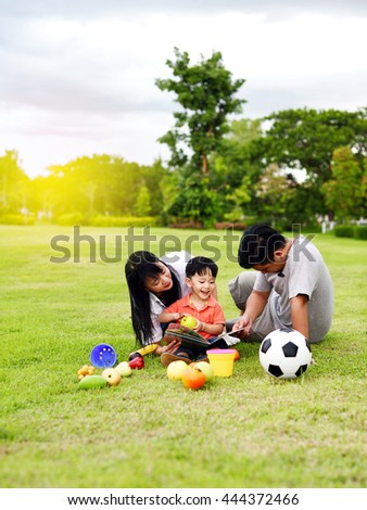 Asian family play together in garden - stock photo