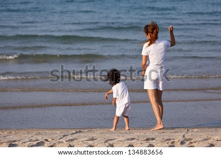 Asian family playing on tropical beach
