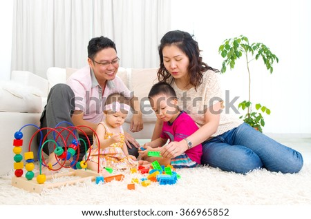 Asian family playing toys - stock photo