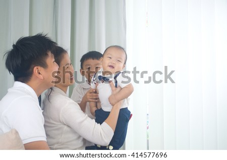 Asian family playing with baby - stock photo