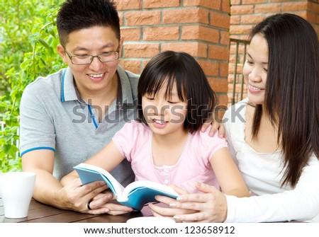 Asian family reading. - stock photo
