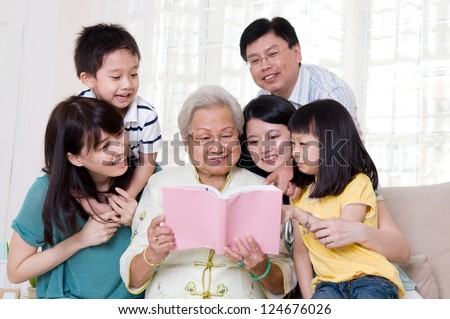 Asian family reading book at home - stock photo