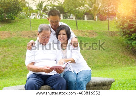 Asian family reading book at outdoor park