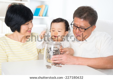 Asian family saving money indoor, grandparents and grandchild living lifestyle at home, financial concept. - stock photo