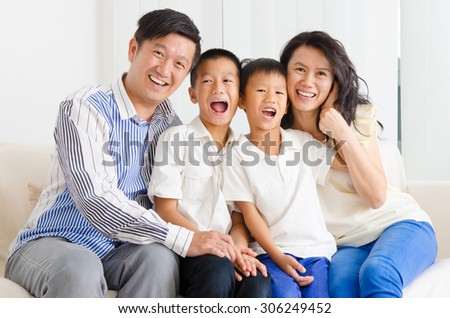 Asian family sitting on sofa