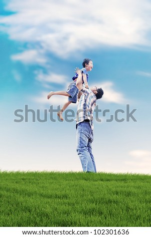 Asian family spending a fun summer day in meadow - stock photo