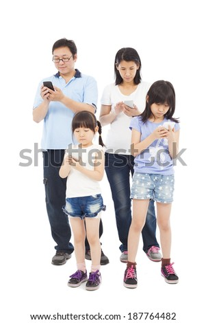 Asian Family standing and using smart phone together - stock photo
